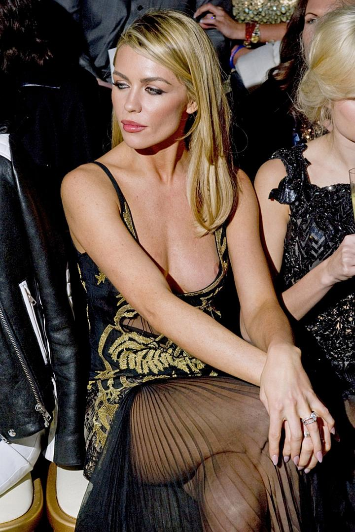 Abbey Clancy suffers nip slip as she sits on the front row at London